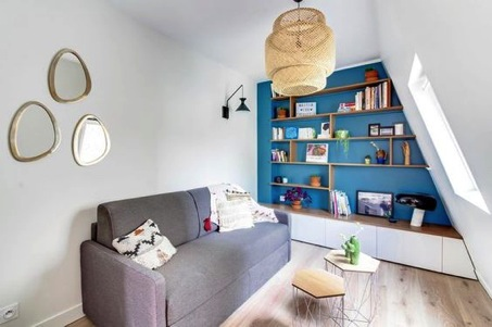 An attic living space with library shelves under the eaves